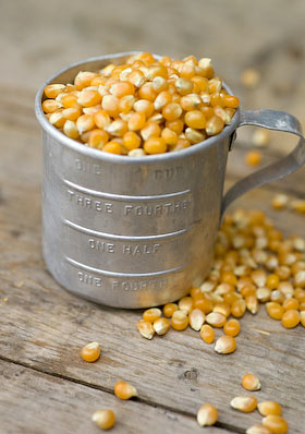 a vintage cup measure filled with popping corn