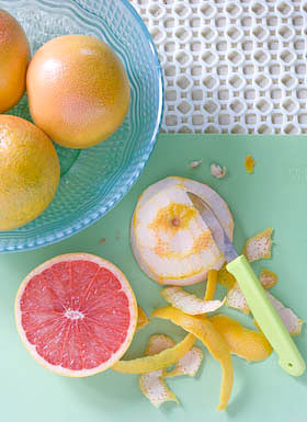 paring the peel from pink grapefruit